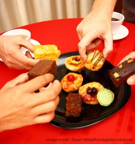 hands picking up delicious pastries from a black plate